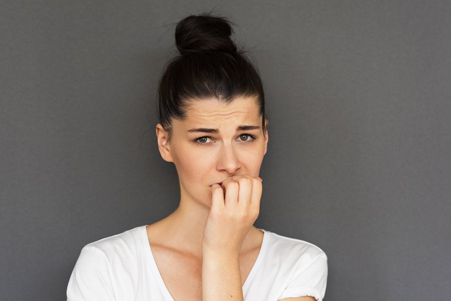 Portrait Of Worried And Sad Woman Looks Stressed, Bites Finger Nails
